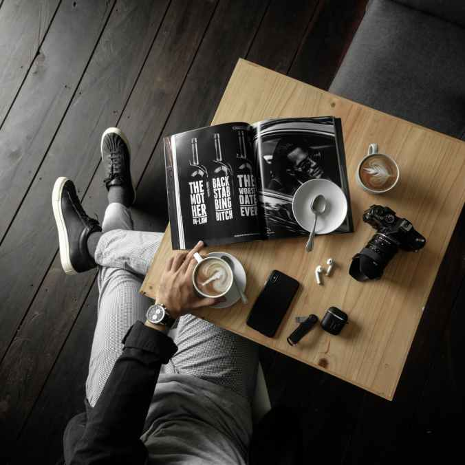 top view of a table with man holding a cup of latte with a magazine camera cellphone and other personal effects